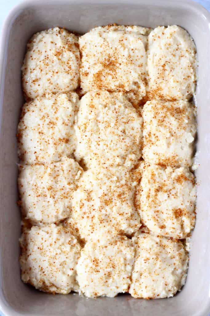 Raw peach cobbler sprinkled with coconut sugar in a grey baking tray