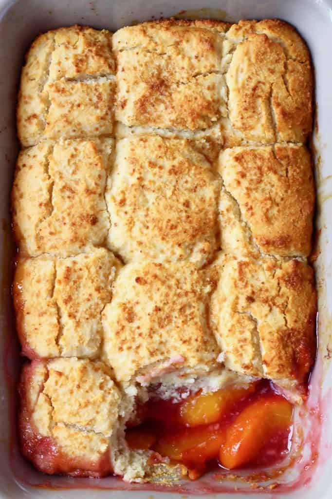 Peach cobbler in a rectangular grey baking tray with a spoonful taken out of it