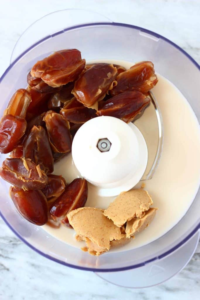 Dates, almond butter and almond milk in a food processor against a marble background