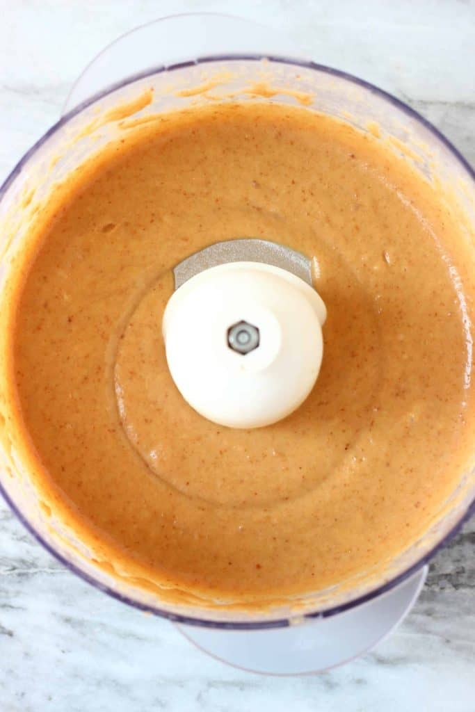 A brown purée in a food processor against a marble background