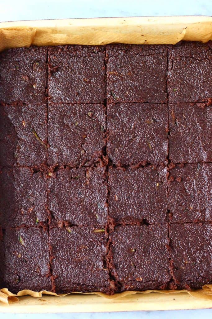 Zucchini brownies in a square baking tray cut into 16 pieces against a marble background