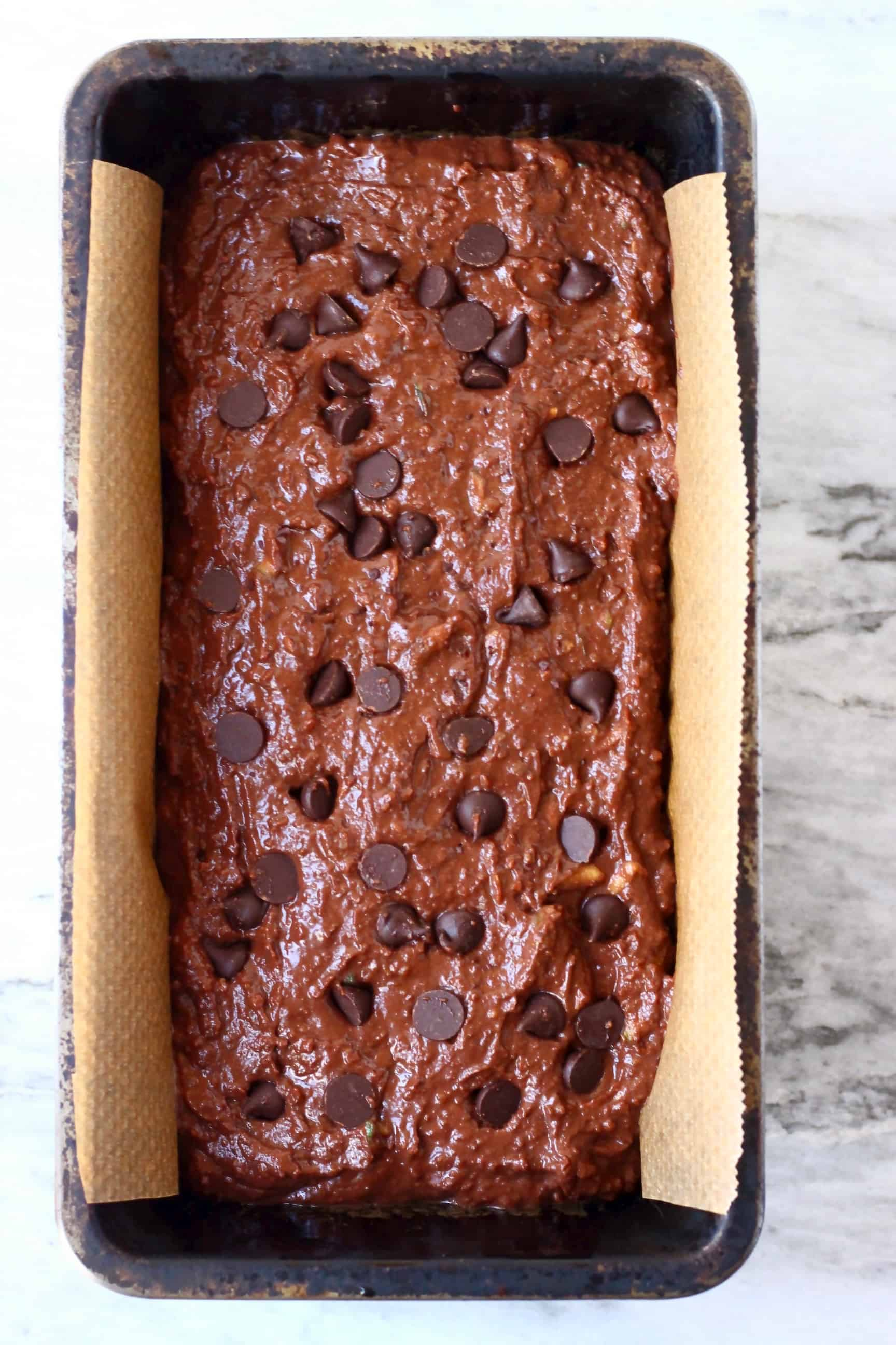 Raw gluten-free vegan chocolate zucchini bread batter studded with chocolate chips in a loaf tin lined with baking paper