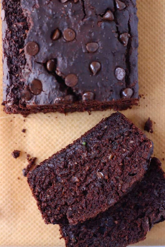 A loaf of chocolate zucchini bread studded with chocolate chips with two slices taken from it against a sheet of brown baking paper