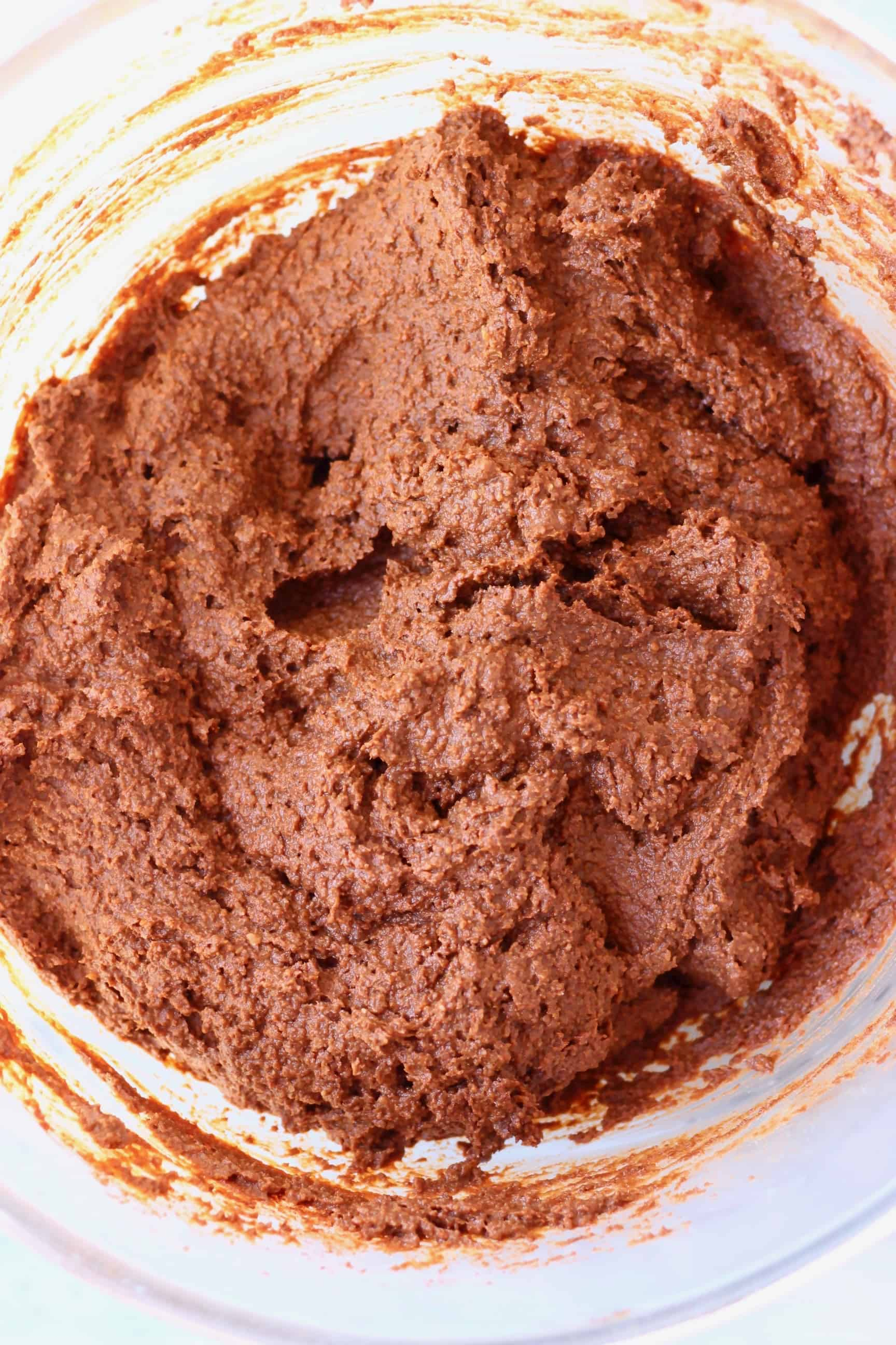 Raw pumpkin brownie batter in a glass mixing bowl