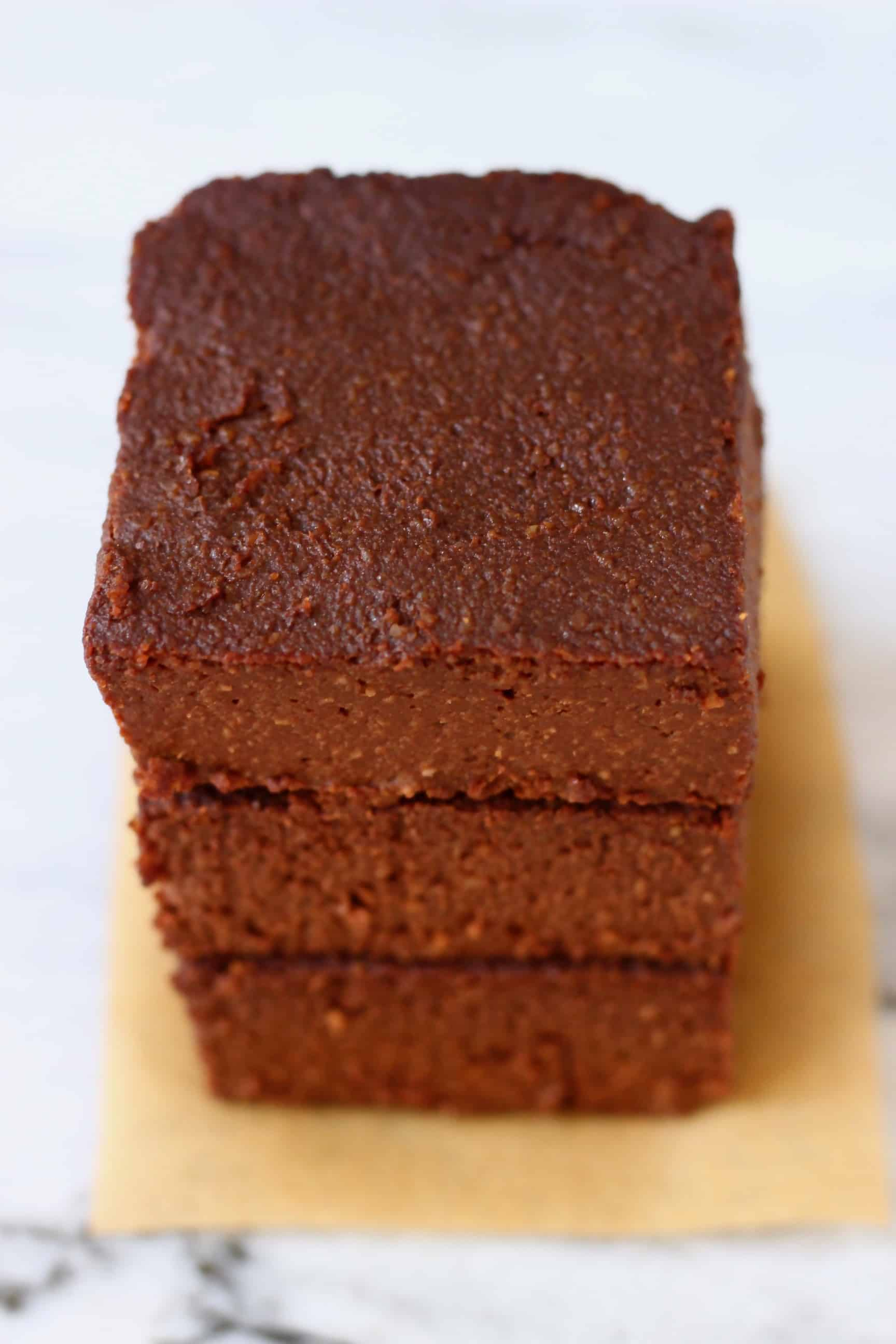 Three pumpkin brownies stacked on top of each other on a sheet of brown baking paper against a marble background