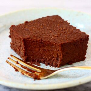 A pumpkin brownie with a mouthful taken out of it on a light blue plate with a gold fork