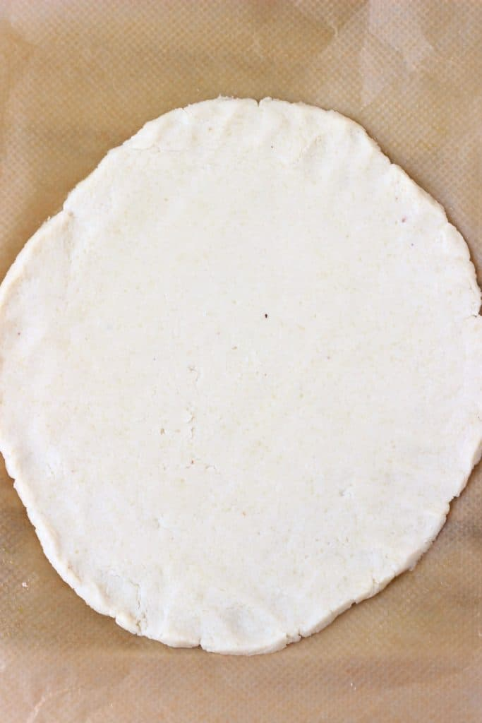 A circle of pastry dough rolled out on a sheet of brown baking paper