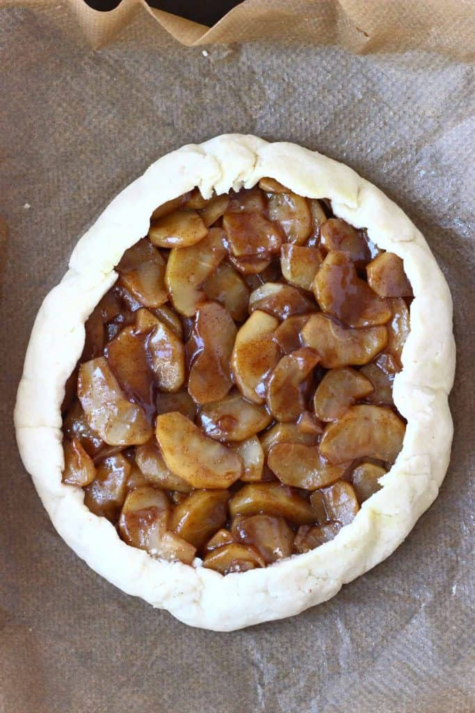 A raw apple galette against a sheet of brown baking paper