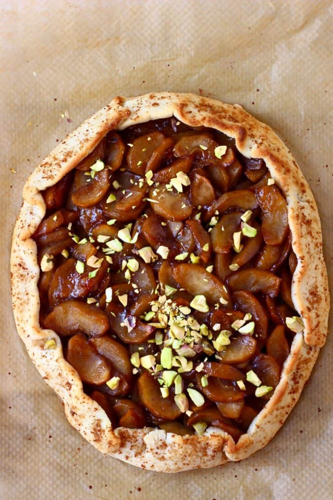 A round galette filled with brown apples sprinkled with pistachio nuts against a sheet of brown baking paper