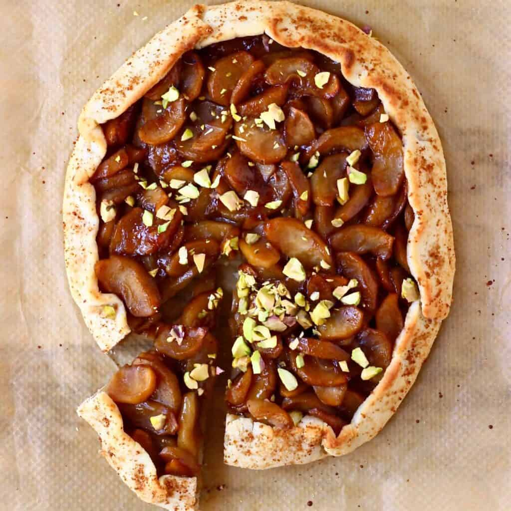 A round galette filled with brown apples sprinkled with pistachio nuts with a slice cut out of it against a sheet of brown baking paper