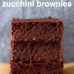 Three zucchini brownies stacked up on top of each other on a sheet of brown baking paper against a grey background