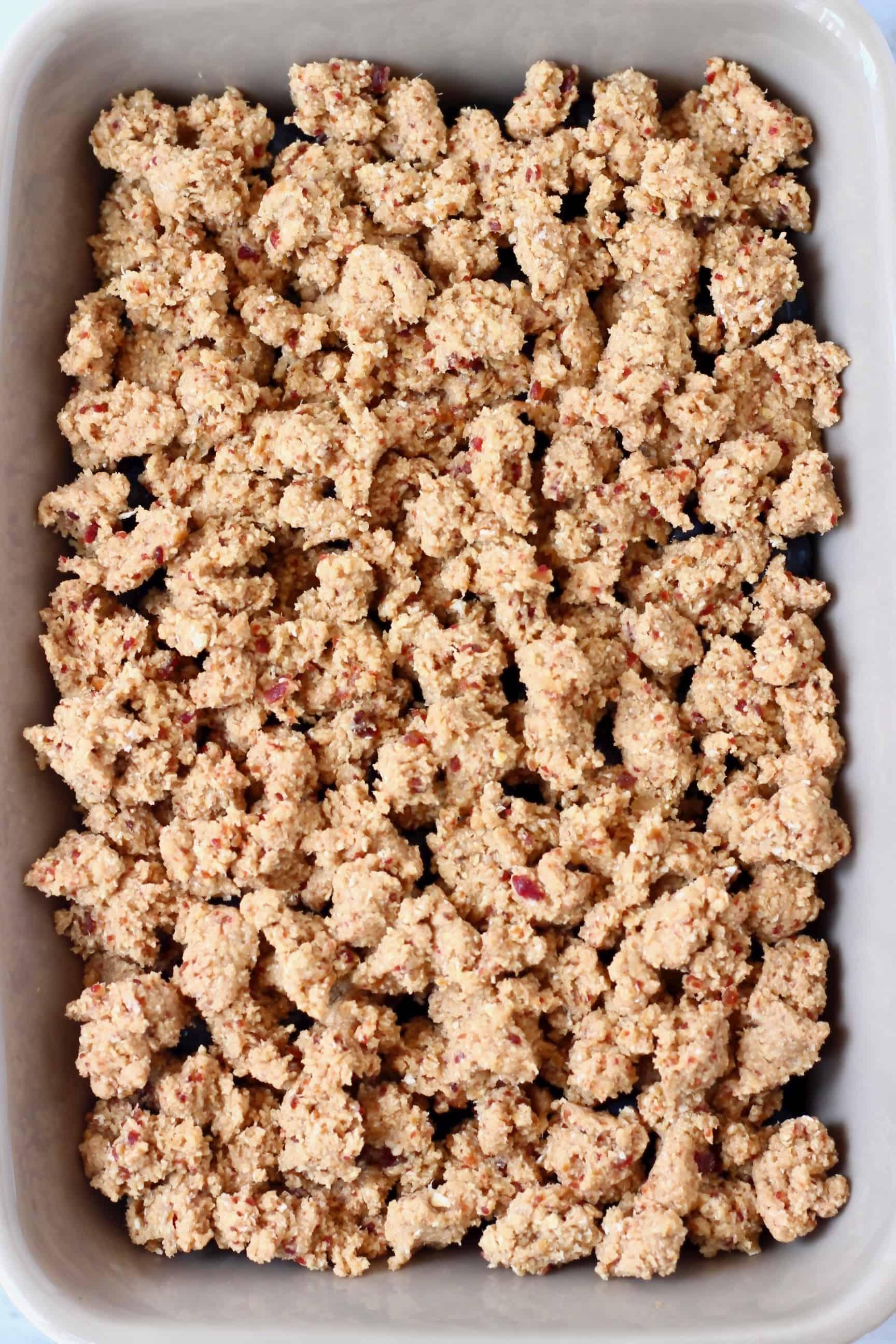 Raw blueberry crisp in a grey rectangular baking