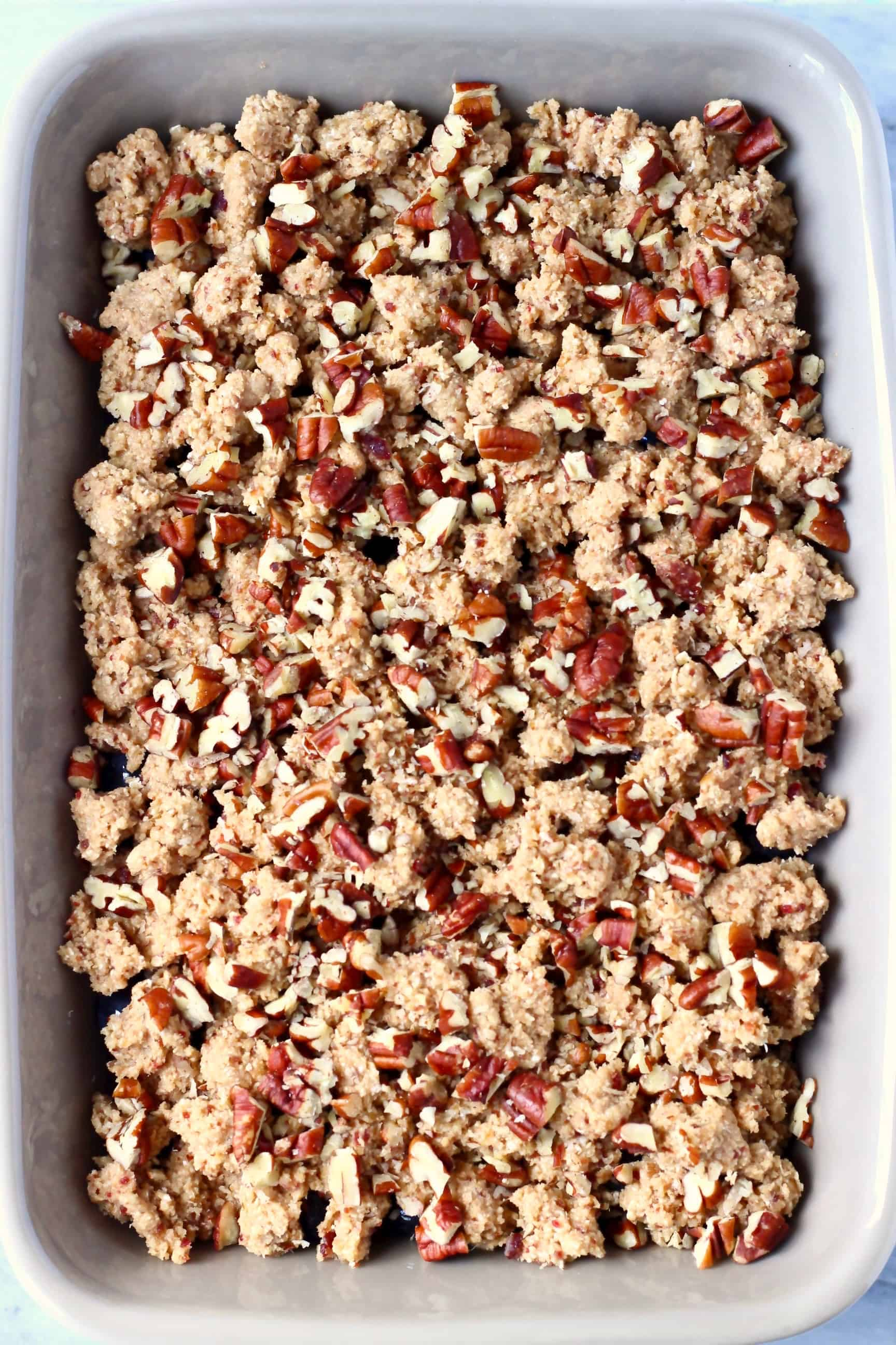 Raw blueberry crisp topped with pecan nuts in a grey baking dish