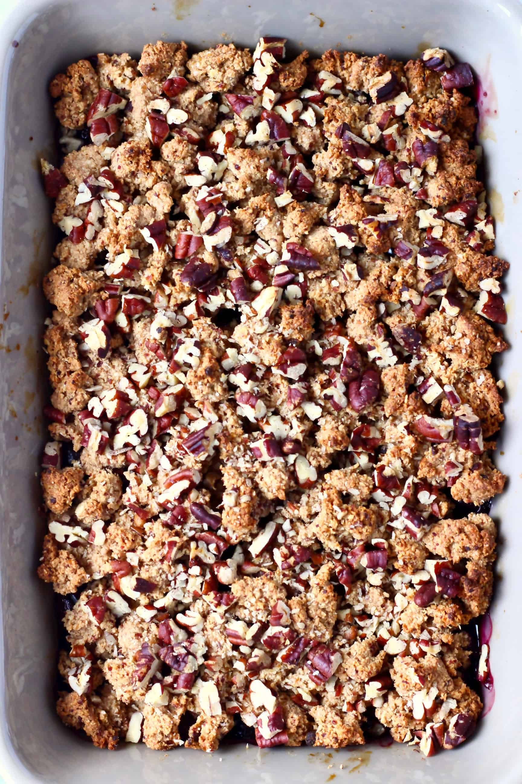 A grey rectangular baking dish with blueberry crisp topped with pecan nuts