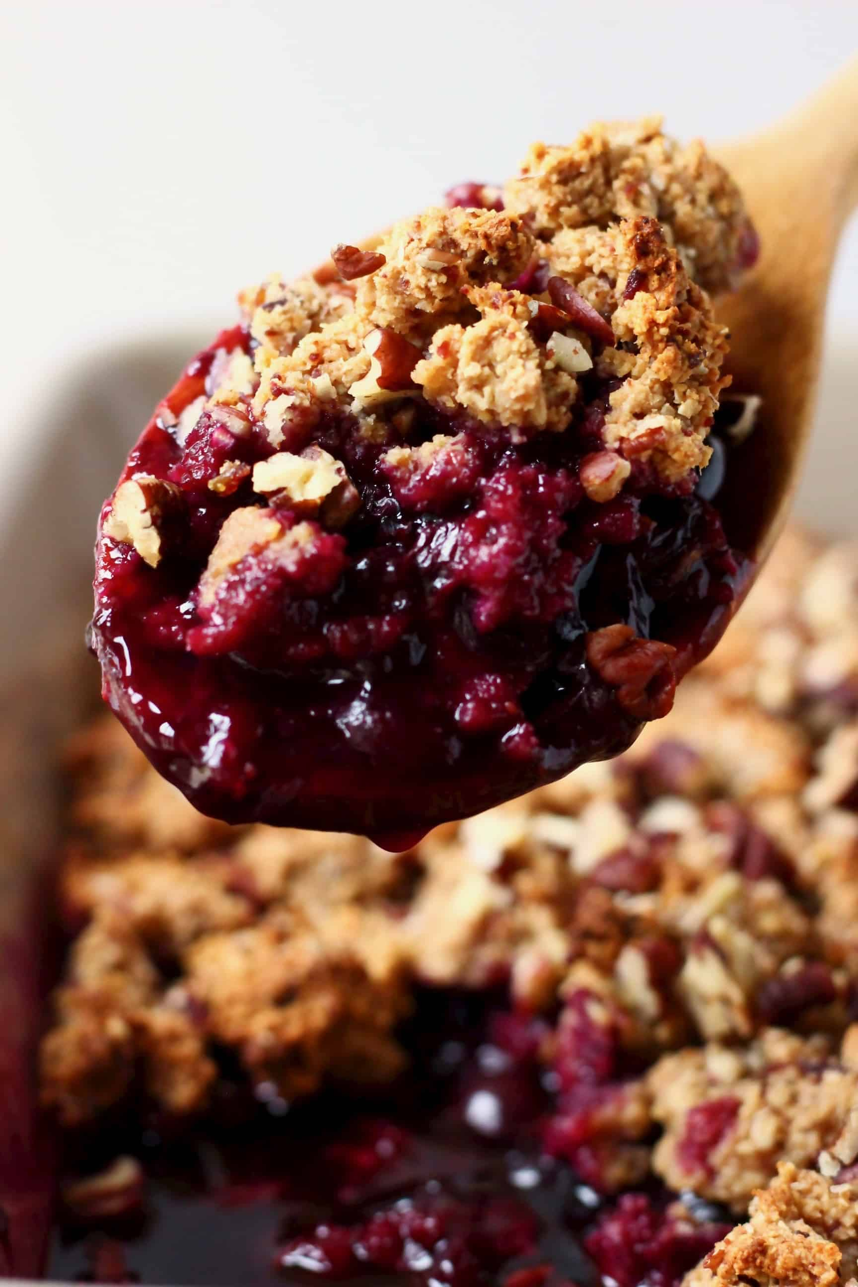 A grey rectangular baking dish of blueberry crisp with a wooden spoon lifting up a mouthful of it