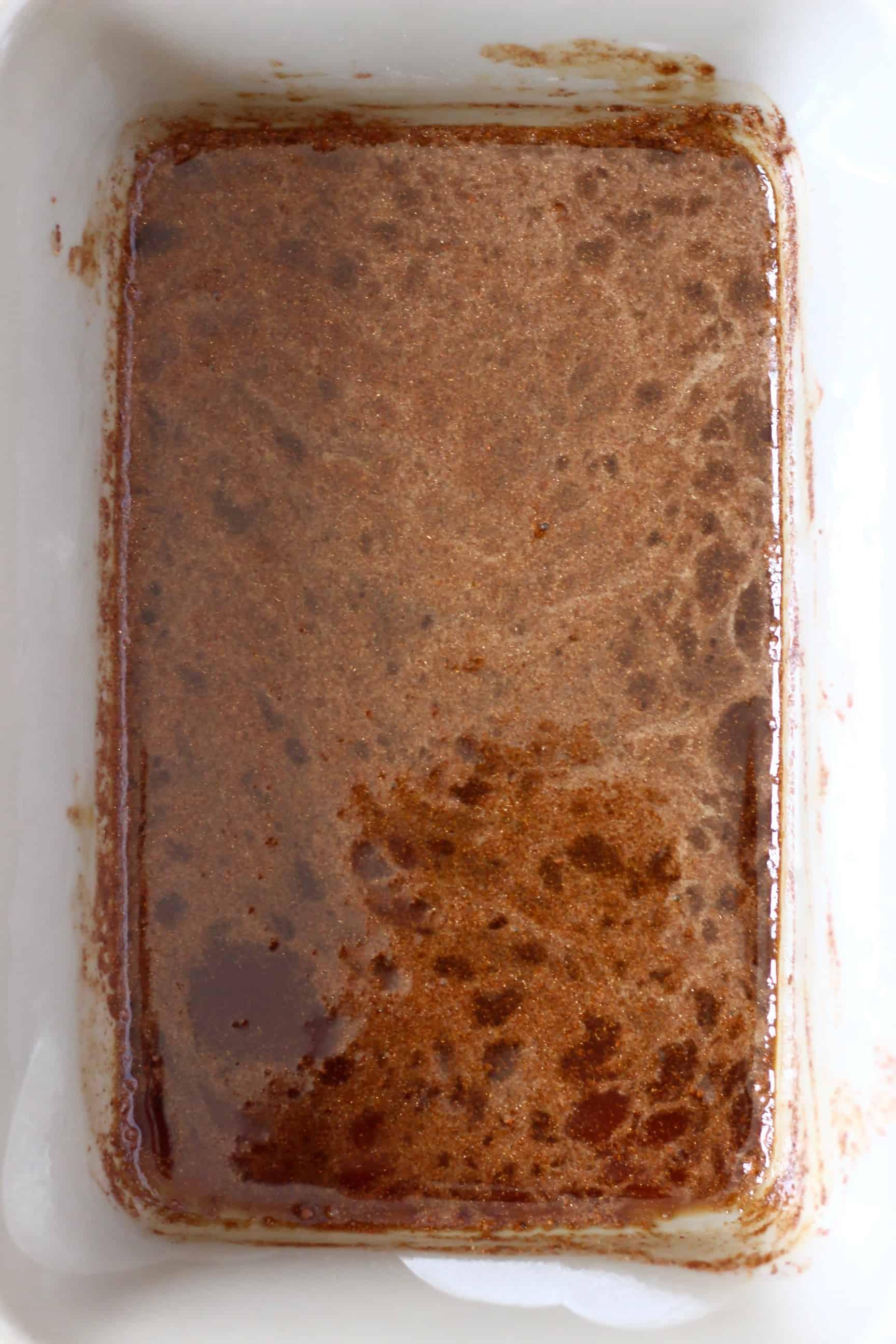 Dark brown caramel sauce for baked apples in a rectangular baking dish