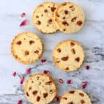 Six round coconut flour cookies with pecan nuts against a marble background scattered with rose petals