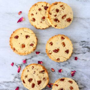 Six round cookies with pecan nuts against a marble background scattered with rose petals