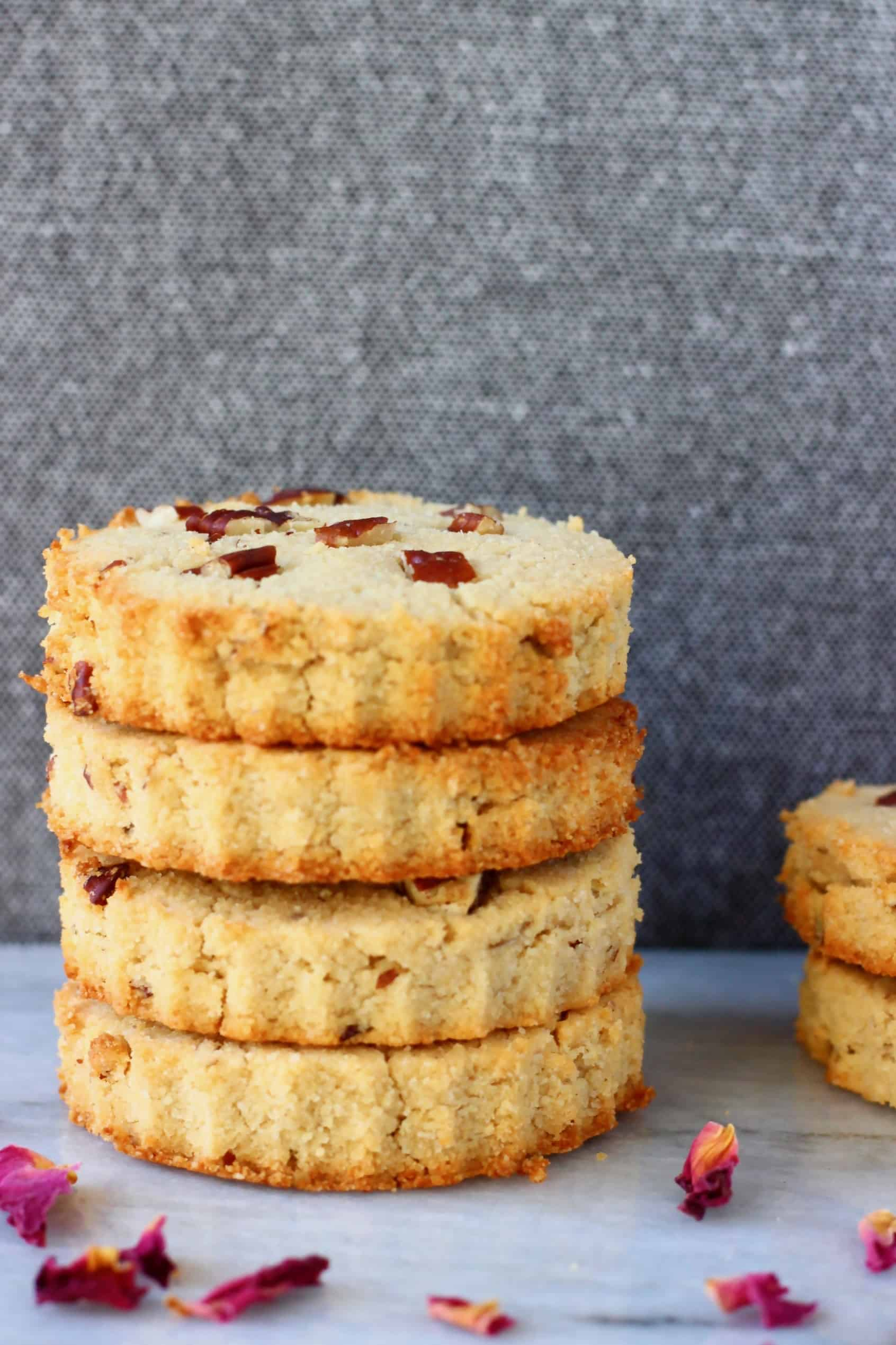 Four circular coconut flour cookies with pecan nuts stacked up on a marble slab against a grey background scattered with rose petals
