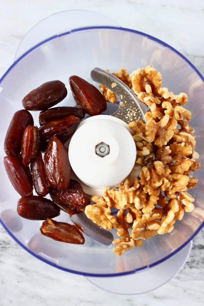 Dates, walnuts and salt in a food processor against a marble background
