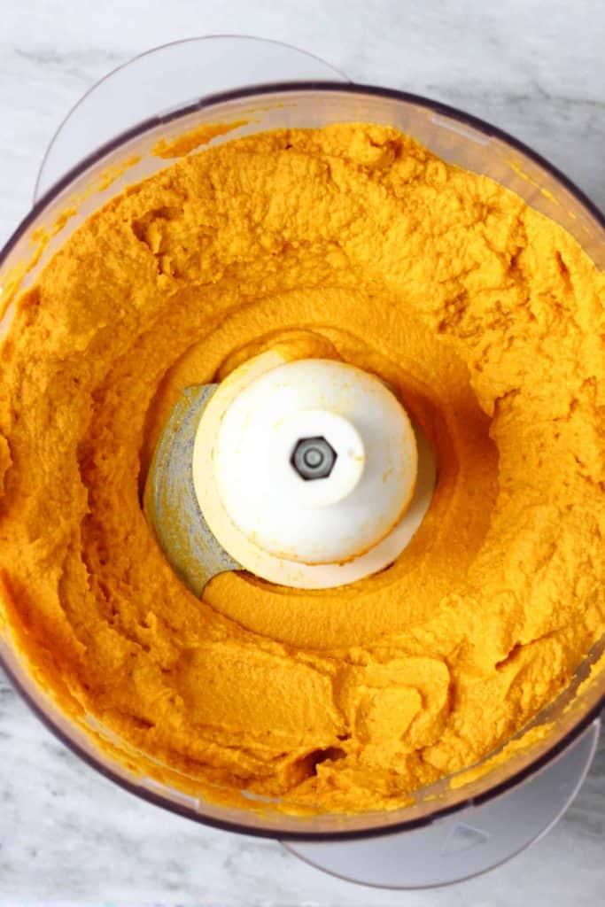 Orange pumpkin pie filling in a food processor against a marble background