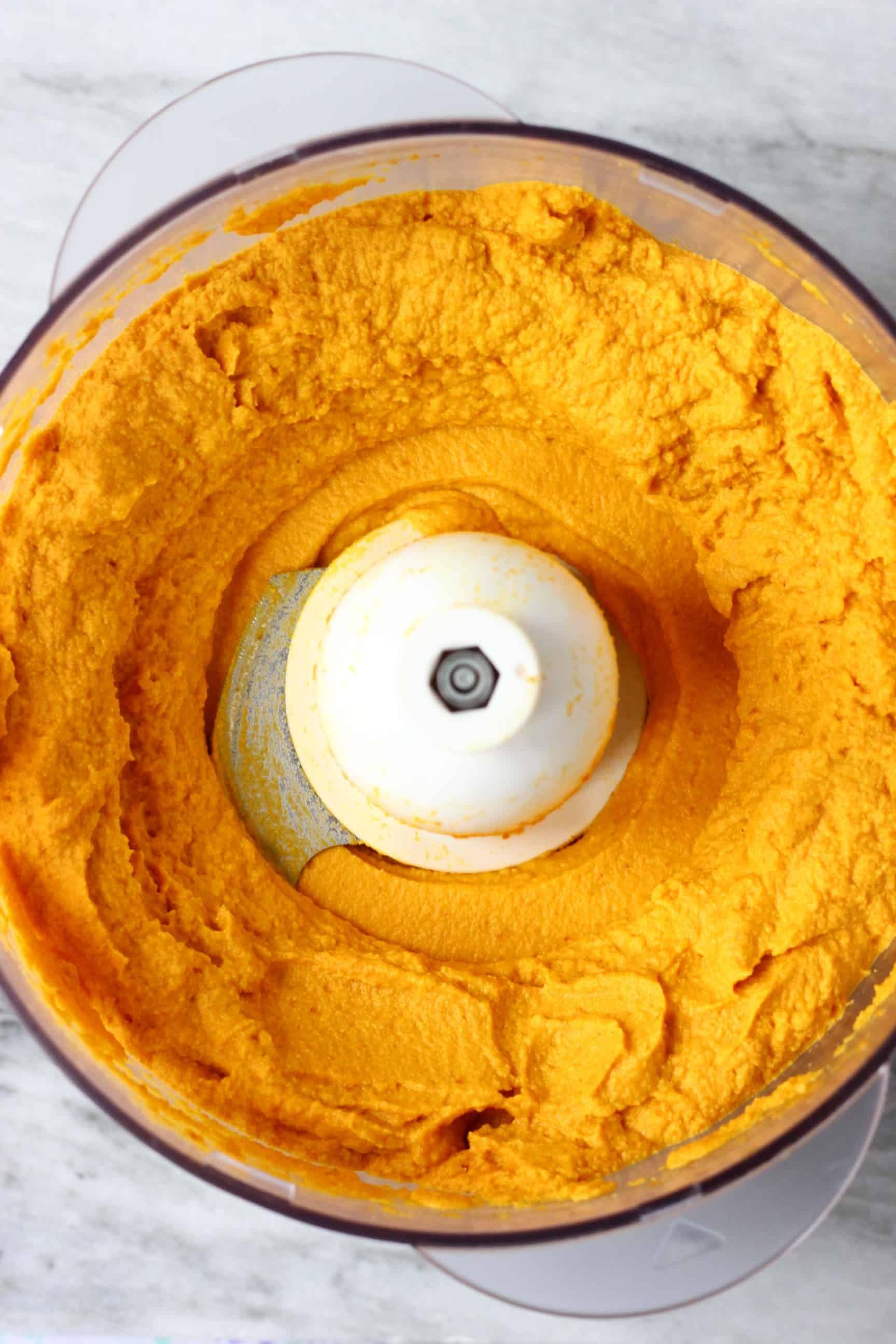 Orange no-bake vegan pumpkin pie filling in a food processor