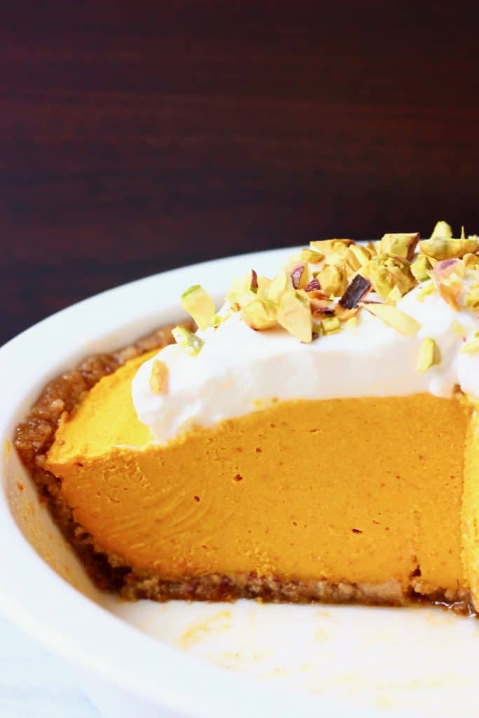 A white pie dish with no-bake pumpkin pie topped with whipped cream and chopped pistachios against a dark brown background