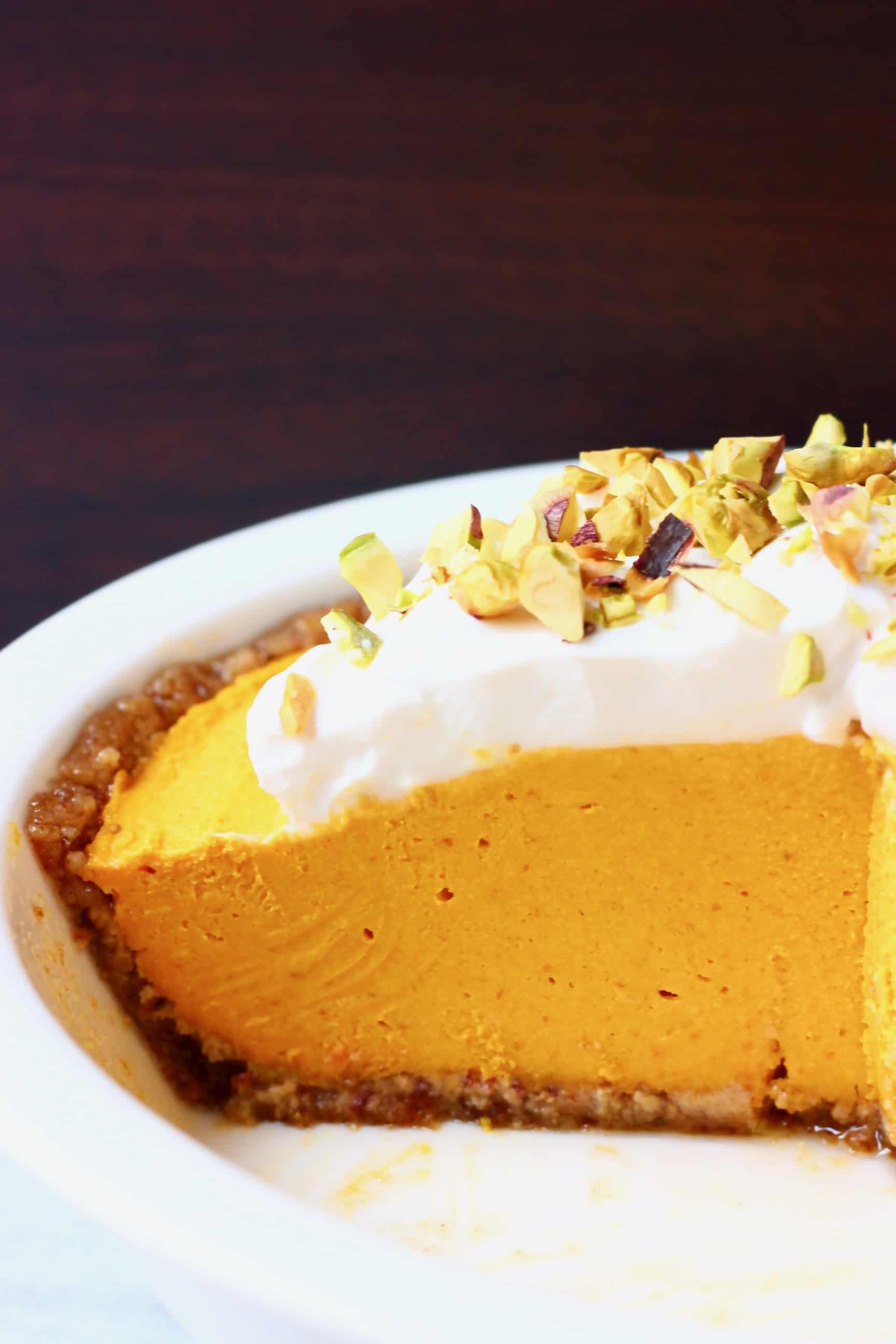 A white pie dish with no-bake vegan pumpkin pie topped with whipped cream and chopped pistachios