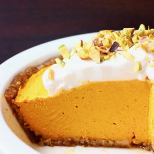 A white pie dish with no-bake vegan pumpkin pie topped with whipped cream and chopped pistachios against a dark brown background