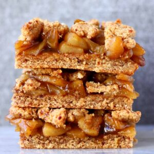 A stack of three apple crumble bars on a marble slab against a grey background