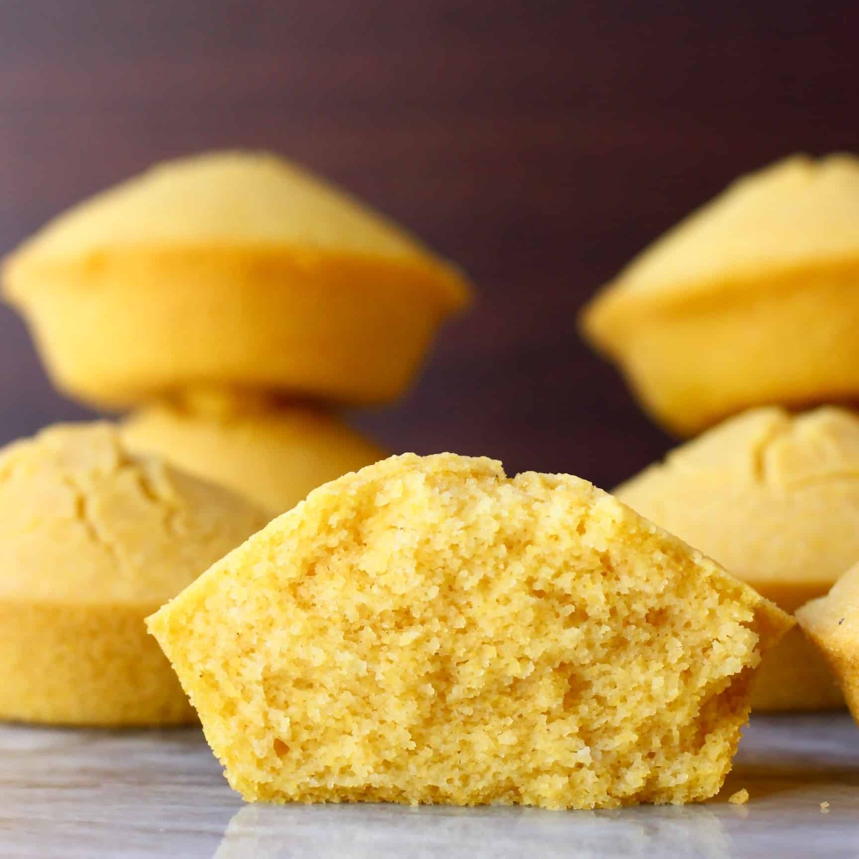 Six gluten-free vegan cornbread muffins with one cut in half on a marble slab against a dark brown background