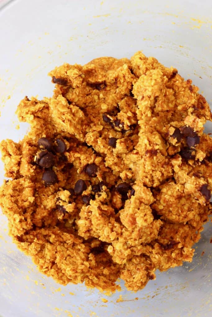 Raw pumpkin cookie dough in a glass mixing bowl against a marble background