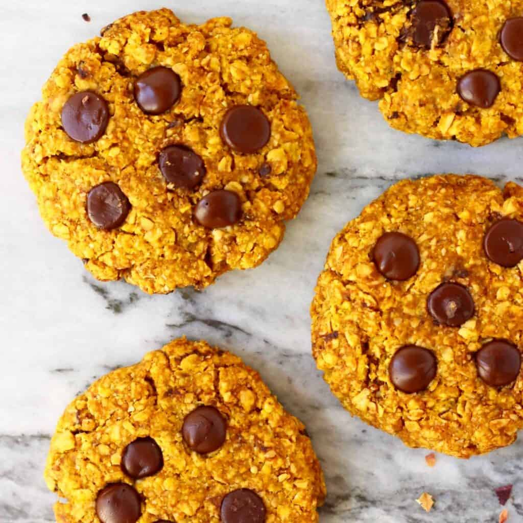 Five pumpkin cookies with chocolate chips against a marble background
