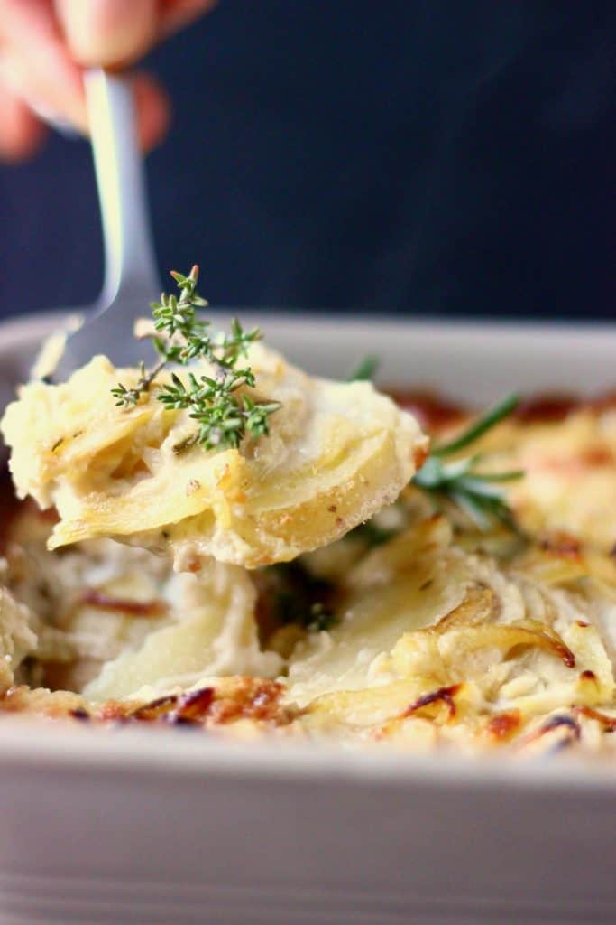 Scalloped potatoes in a grey baking dish with a silver spoon lifting up a mouthful of it against a black background