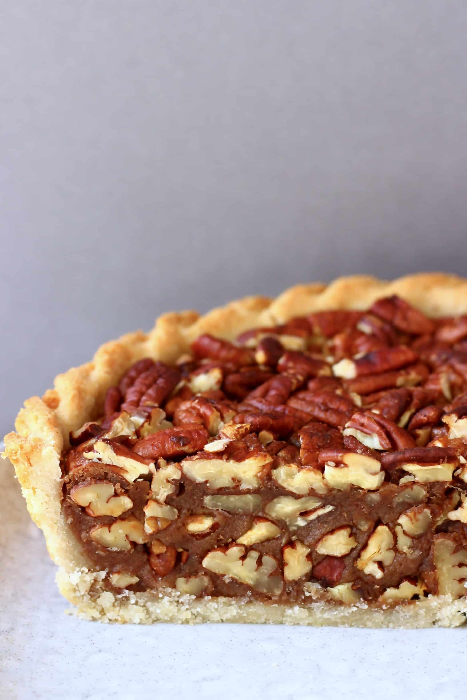A sliced vegan pecan pie topped with pecan nuts