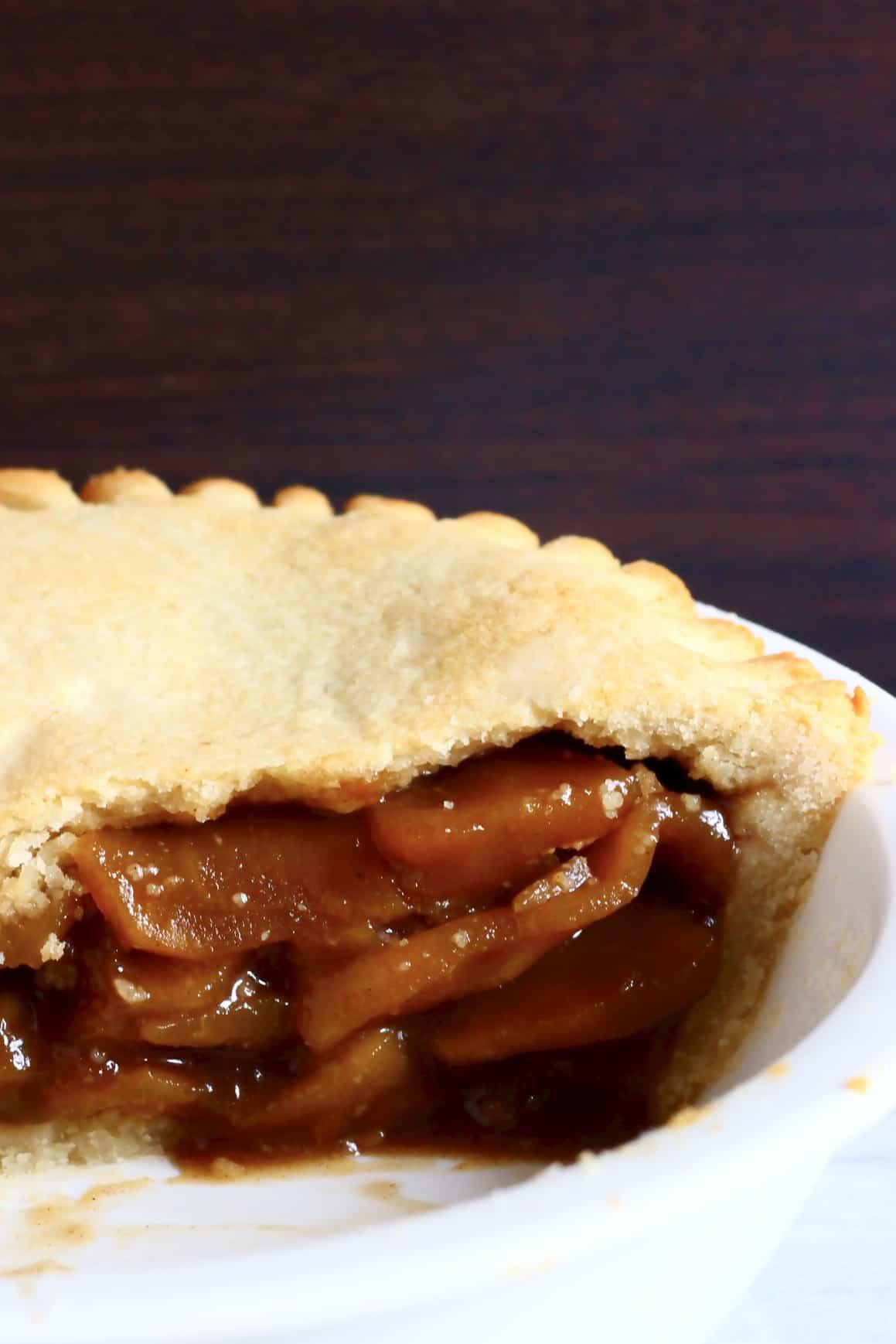 A sliced gluten-free vegan apple pie in a white pie dish