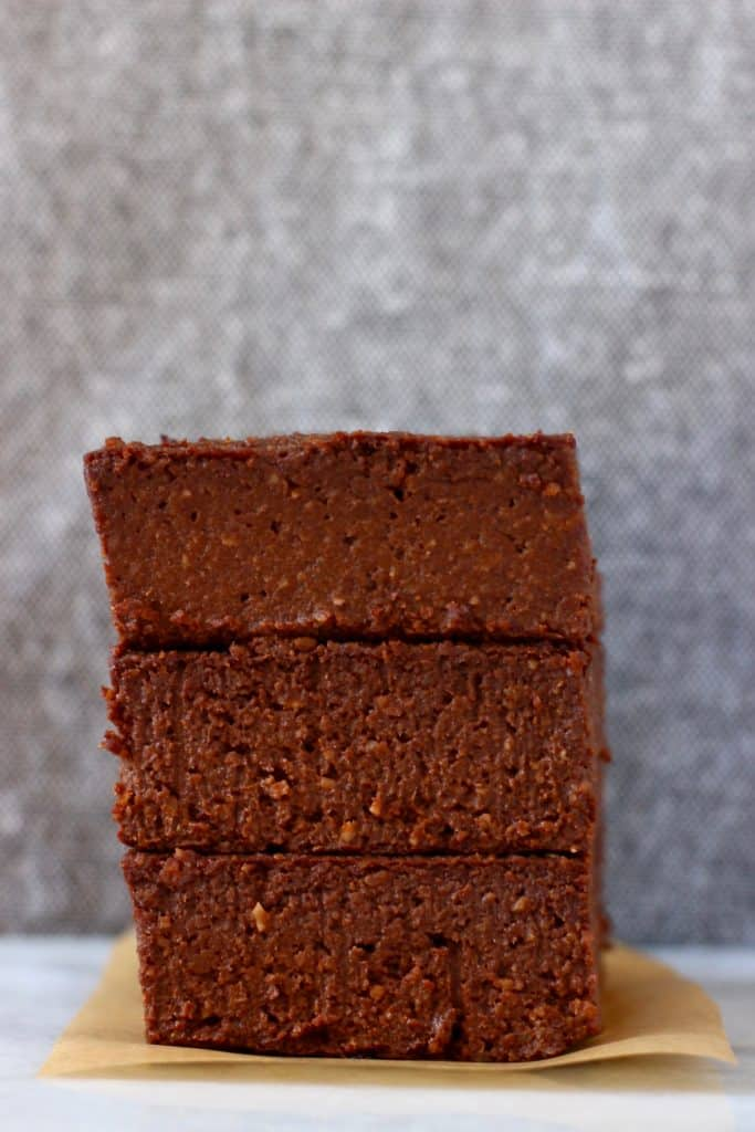 Three pumpkin brownies stacked on top of each other on a sheet of brown baking paper against a grey background