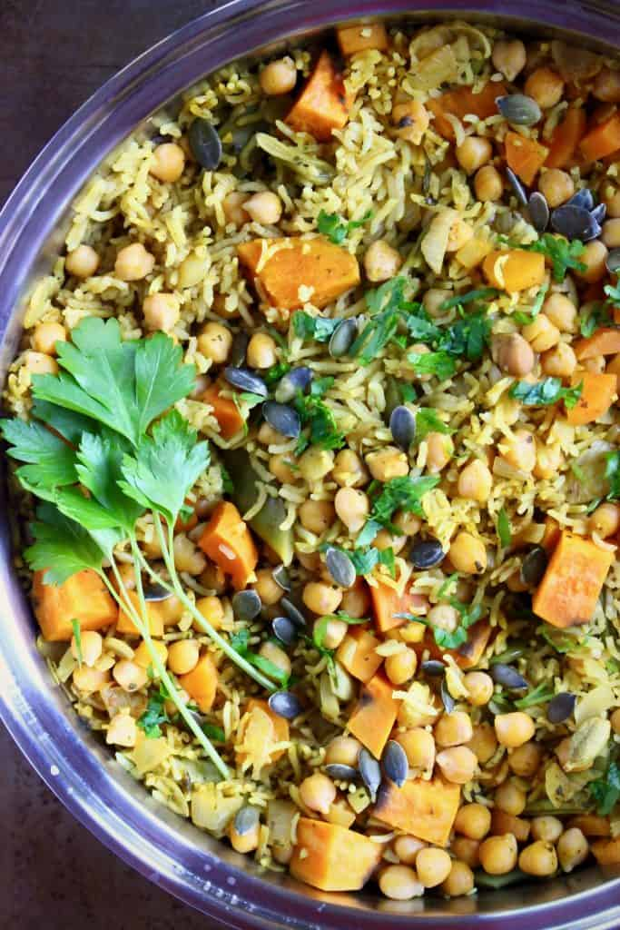 Yellow biryani rice with chopped pumpkin, chickpeas and pumpkin seeds in a silver saucepan