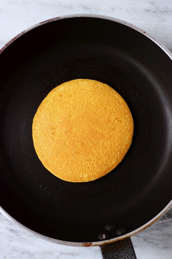 A golden brown cornmeal pancake in a black frying pan against a marble background