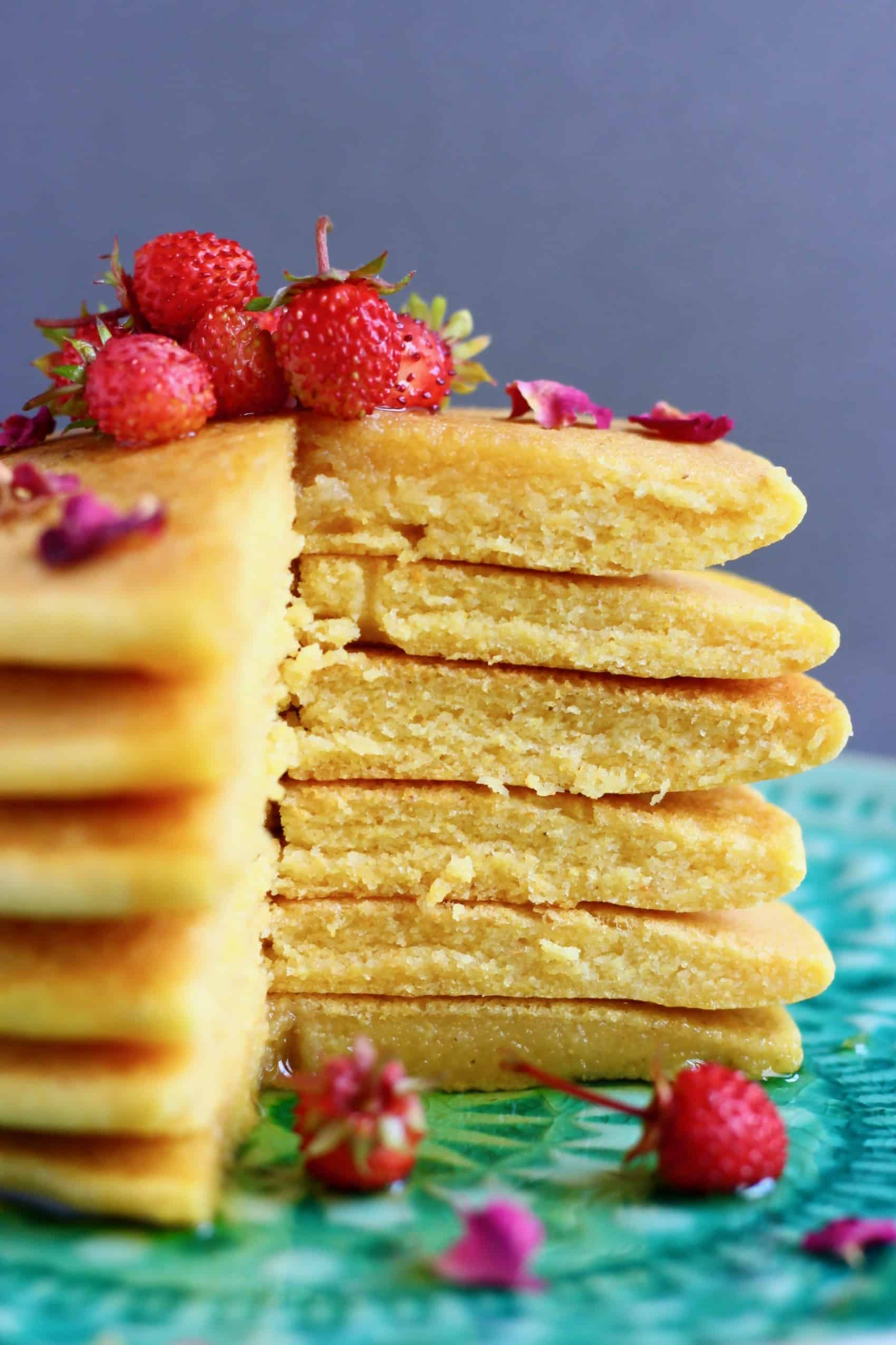 A stack of gluten-free vegan cornmeal pancakes with a slice cut out of them topped with rose petals and small strawberries on a plate