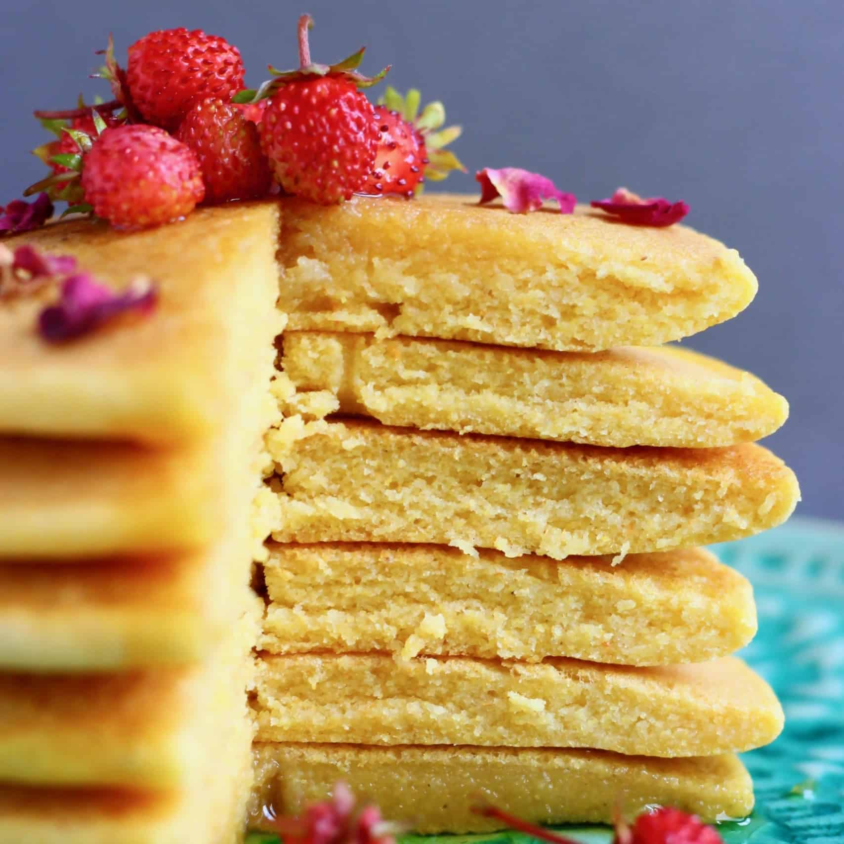 A stack of cornmeal pancakes with a slice cut out of them topped with rose petals and small strawberries on a green plate against a grey background