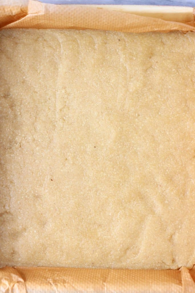 Raw shortbread cookie dough in a square baking tin lined with baking paper