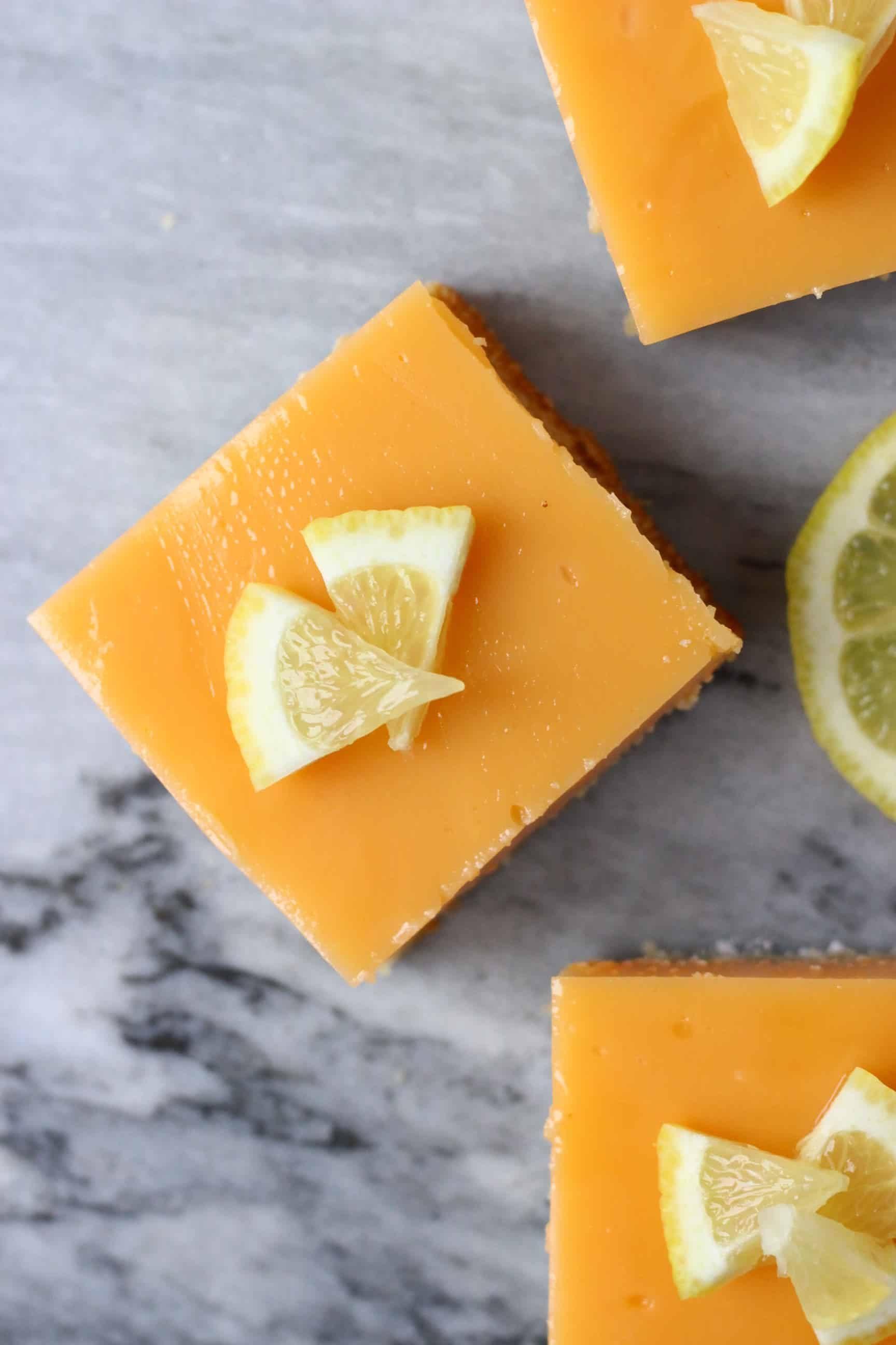 Three gluten-free vegan lemon bars topped with lemon wedges