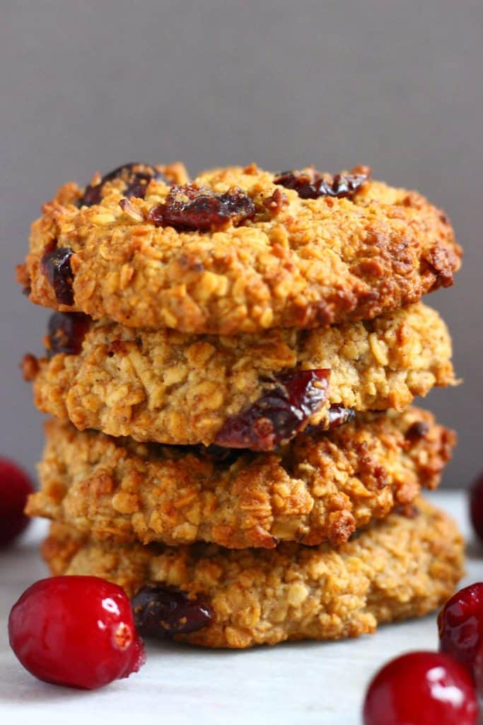 A stack of four oatmeal cookies with dried cranberries against a grey background