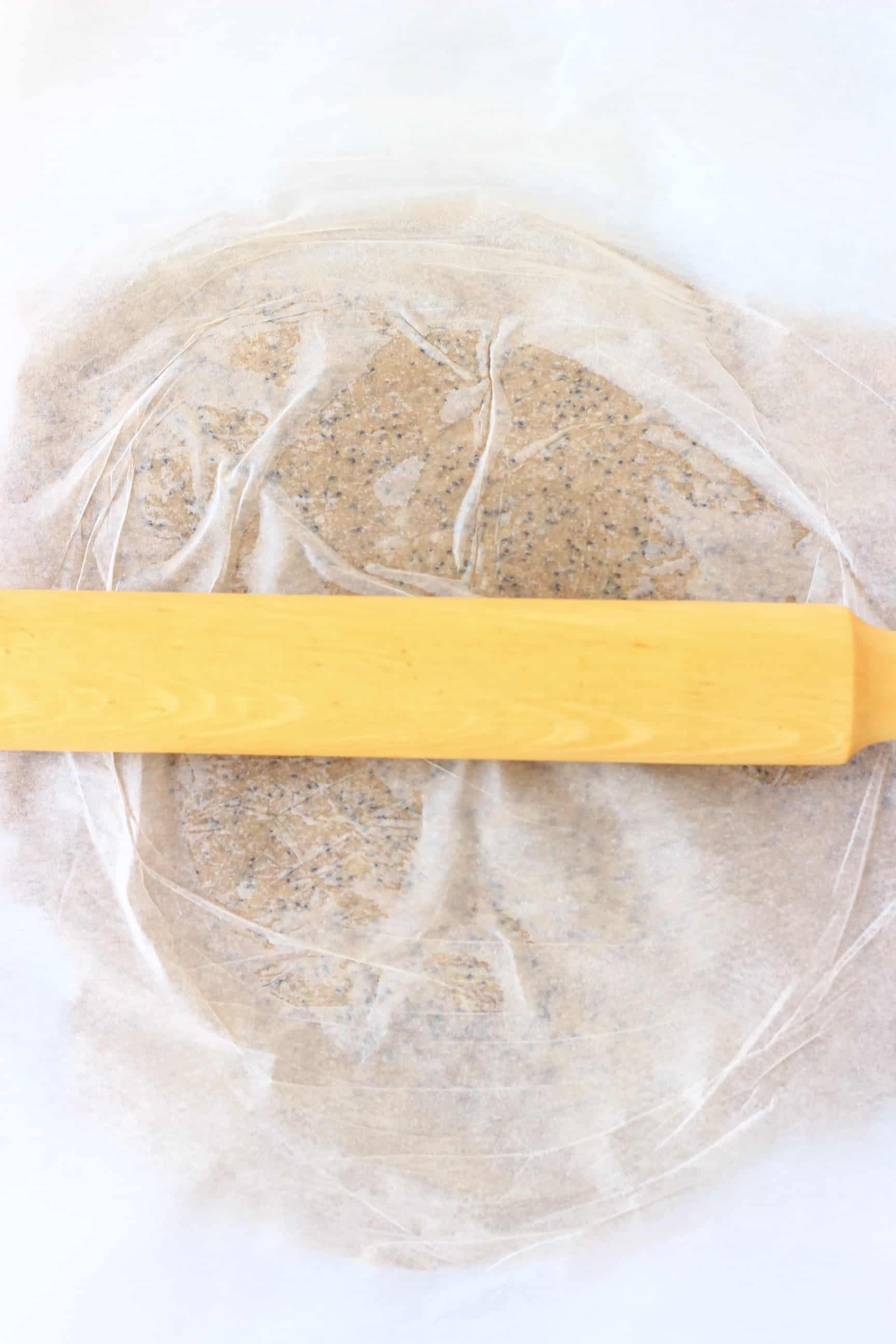 Raw gluten-free vegan crackers mixture between two sheets of baking paper being rolled out with a rolling pin