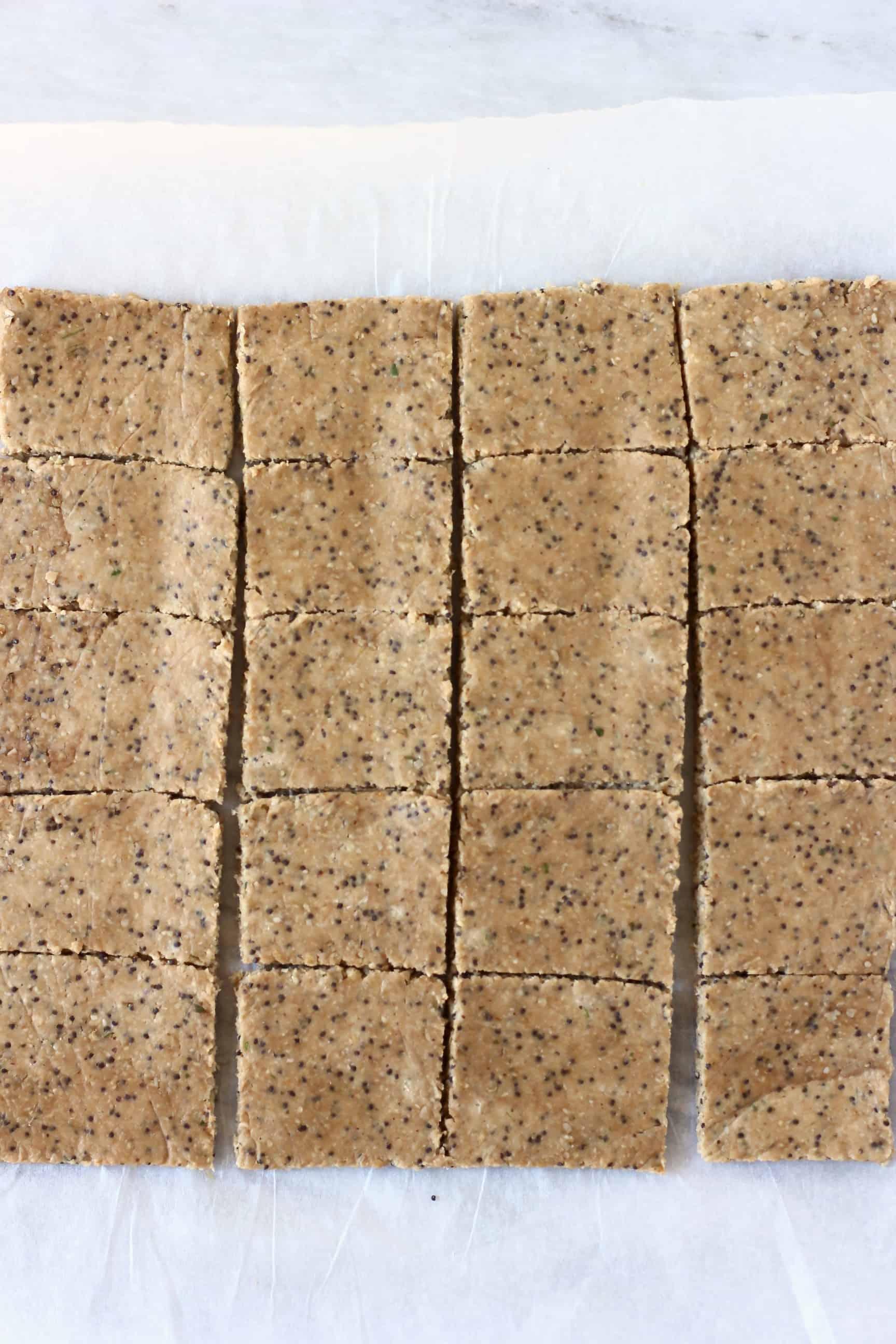 Squares of raw gluten-free vegan cracker mixture on a sheet of baking paper