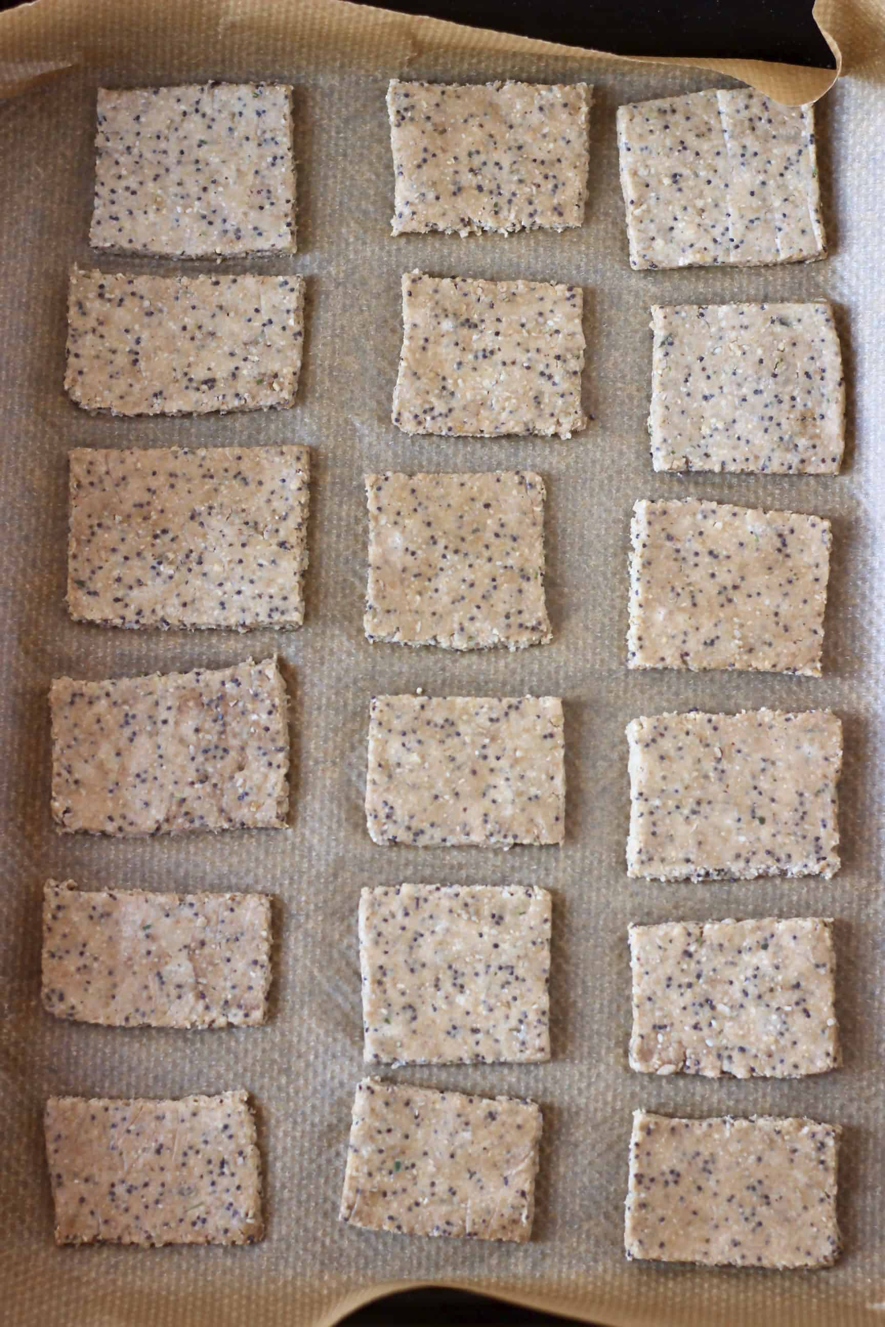 Eighteen square raw gluten-free vegan crackers on a baking tray lined with baking paper