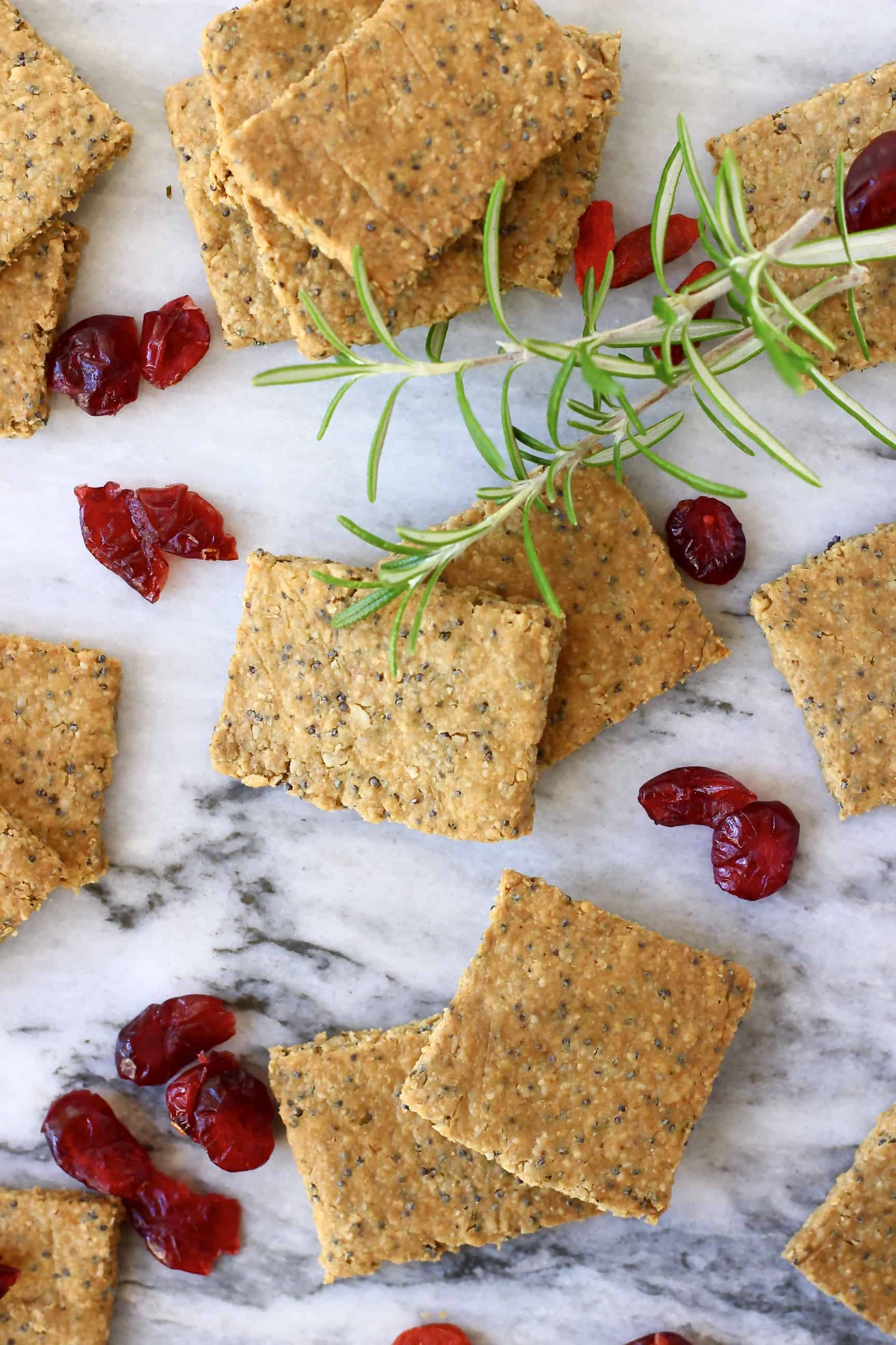 Several square gluten-free vegan crackers with dried cranberries and rosemary on a marble background