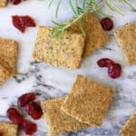 Several square gluten-free vegan crackers with dried cranberries and rosemary