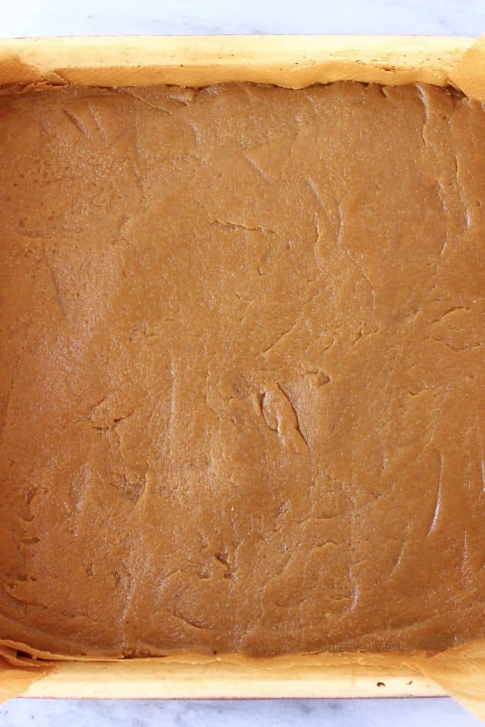 A layer of brown caramel in a square baking tin